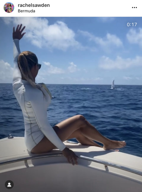 Woman on boat waves to whales in water